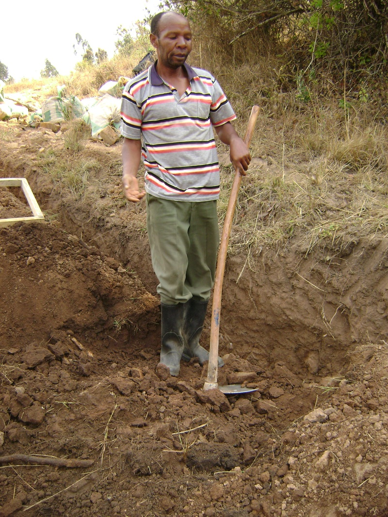 """Gallus, retired water technician, digs out the wall of the trench to hold a concrete and brick box for a """"gate valve"""""""