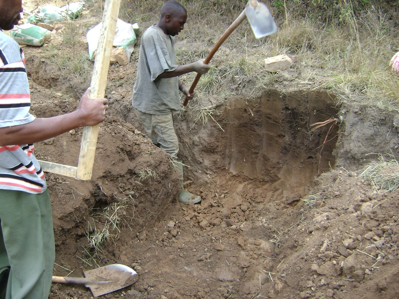 Moses and Gallus dig out the trench wall for a gate valve