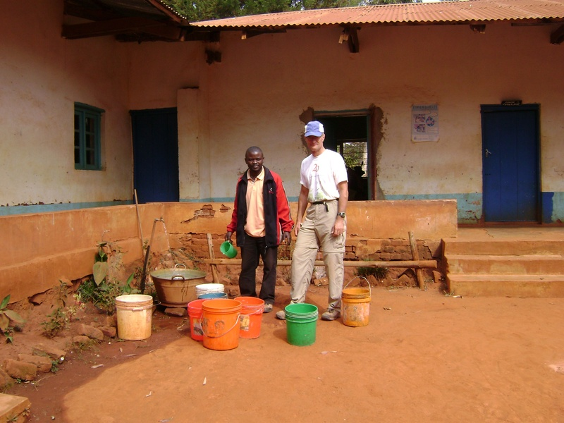 Carrying water in buckets from the Clinic to refill a small water tank on site to mix concrete