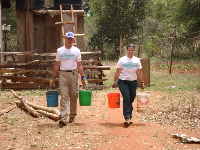Carrying water in buckets from the Mission House to refill a small water tank on site to mix concrete